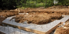 The footings are poured. Note the rebar protruding from the footing. This will tie the upper part of the structure to the footing.